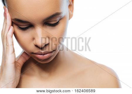 Having a headache. Upset disappointed sad Negroid woman touching her head while standing against white background and suffering from a headache