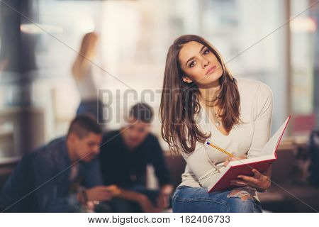 Beautiful young student with book studying or preparing for exams in a cafe