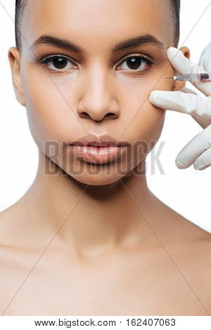 On the way of improvement. Pleasant involved young Negroid woman standing isolated in white background and expressing confidence while getting the injection in her face
