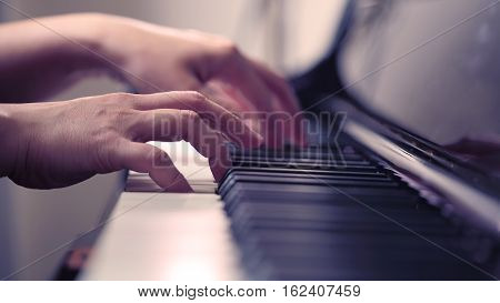 Scene of pianist hands from beside angle playing piano Photo in vintage colors style. Selective focus.