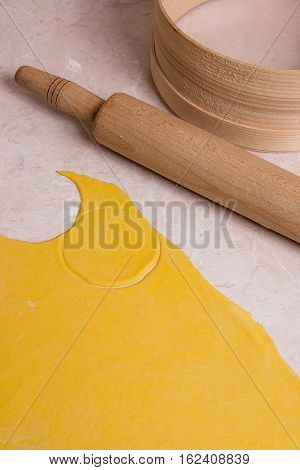 Rolling Pin, Sieve And Rolled Out Dough On Light Marble Background..