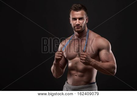 Muscular man with measurement tape, isolated on dark grey background