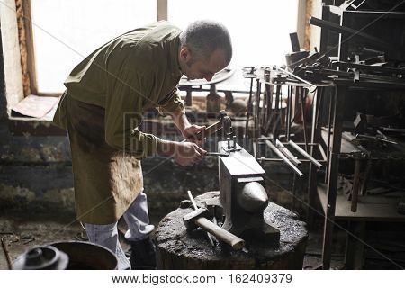 The blacksmith in the production of Handicrafts made of metal on the anvil in the workshop poster