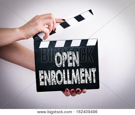 Open enrollment. Female hands holding movie clapper.