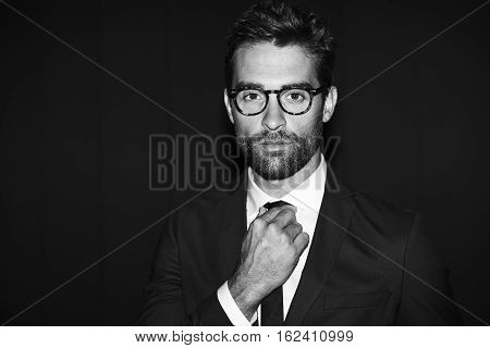 Guy adjusting tie in black and white shot portrait