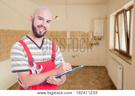 Young Fitter Writing Something On Clipboard