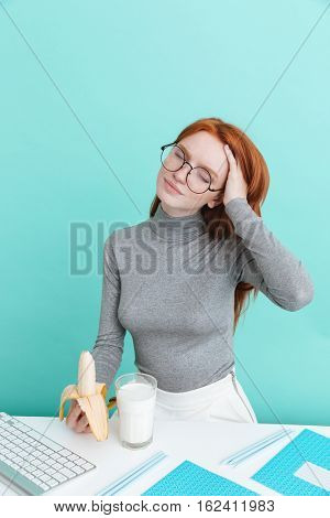 Relaxed young woman in glasses drinking milk and eating banana over blue background