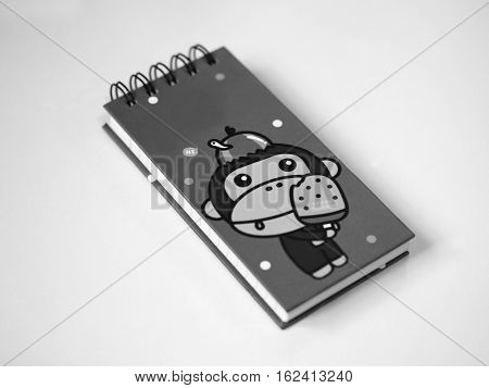 BLACK AND WHITE PHOTO OF NOTEBOOK WITH WHITE BACKGROUND