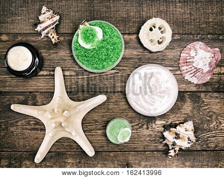 Peeling and spa cosmetics and accessories: sea salt, loofah, natural scrubs, skin care cream with conches and starfish on wooden planks. Vintage toning