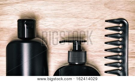Hair care and styling products with comb on natural wood surface. Toned image