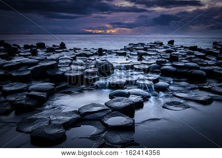 The Giant's Causeway at night as the last light of the setting sun appears over the horizon in Northern Ireland.