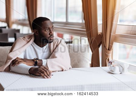 Waiting for an interlocutor. Charming handsome young man sitting in the cafe and looking at the window while being covered with a blanket and being involved in his thoughts