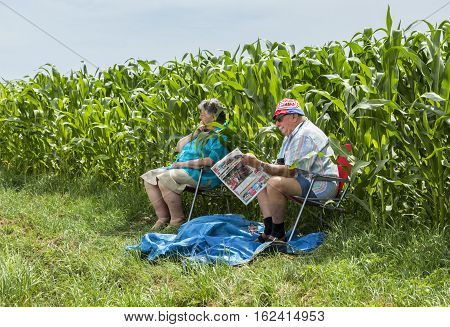 QUIEVYFRANCE- JULY 07 2015: Unidentified old couple sitting by the corn field and waiting for the peloton during the stage the stage 4 of Tour de France in Quievy on 07 July 2015.