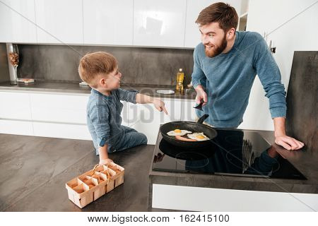 Photo of handsome bearded father dressed in blue sweater cooking at kitchen with his little cute son