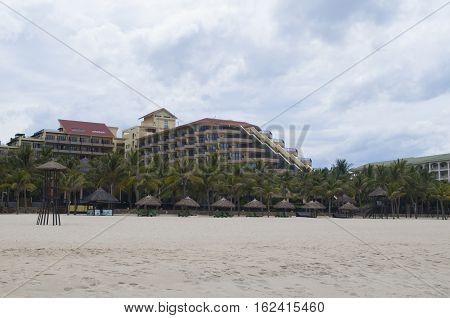 Hotel palms straw umbrellas and white sand in the My Khe beach Danang Vietnam
