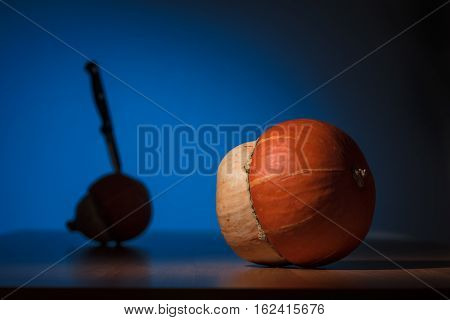 Lited pumpkin in front of another pumpkin in shadow with knife in it