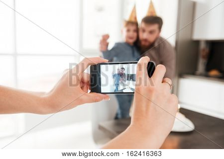 Image of cheerful bearded young father in the kitchen with his birthday little son making selfie
