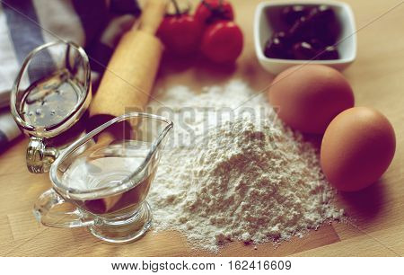 Preparing Homemade Fresh Pasta Dough with Black Olives Tomatoes and Olive Oil with Herbs closeup on Wooden Table. Focus on Top of Flour