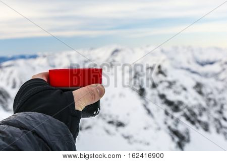 Tourist Holding A Cup Of Tea In The Winter In The Mountains.