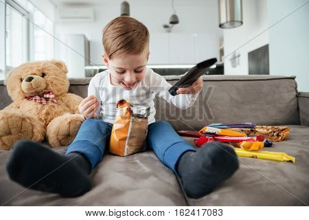 Image of little boy sitting on sofa with teddy bear at home and watching TV while eating chips. Holding remote control.