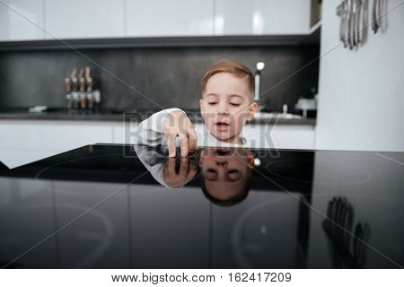Image of dangerous situation in the kitchen. Little boy playing with electric oven.