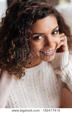 Sharing positive atmosphere. Charming positive delighted African American woman sitting in the cafe and being covered with a blanket while smiling sincerely