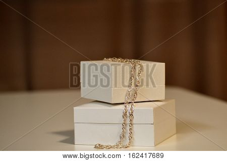 Two gift boxes with a chain of gold