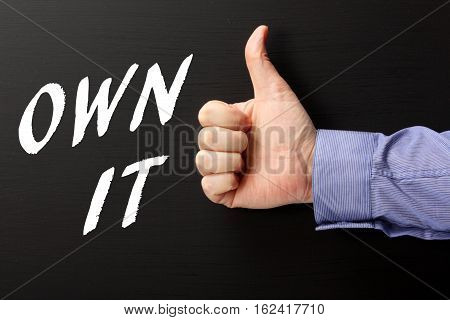 Male hand in a business shirt giving the thumbs up sign to the words Own It written on a blackboard as a reminder to take ownership