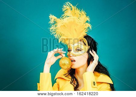Pretty girl or cute sexy woman has brunette hair in golden festive carnival mask with feathers and yellow coat on blue background hold decoration ball