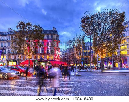ParisFrance - 27 November 2016: Dusk image of blurred pedestrians crossing the street on the famous Champs Elysees Boulevard in Paris festive decorated during the winter holidays.