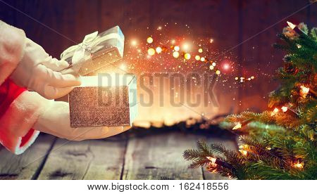 Santa Claus opens gift box, holding a gift in his hands over wooden background with blinking garland and Christmas tree. Xmas scene with magic gift, wishes.