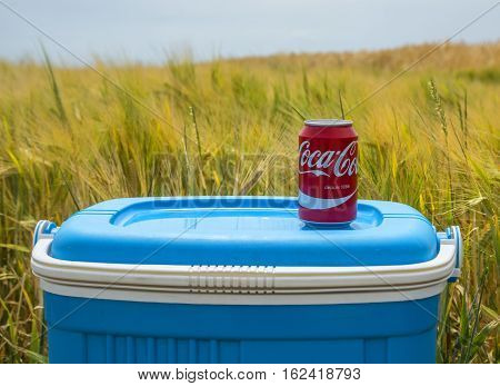 Quievy, France - July 72015: Illustrative editorial image of a Coca Cola can located on a fridge box in a field near a cobblestone road during the stage 4 of Tour de France 2015 in Quievy France on 07 July.