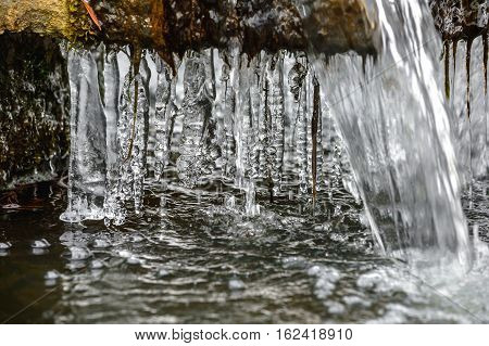Ice Icicles On A Freezing Fountain In Winter.