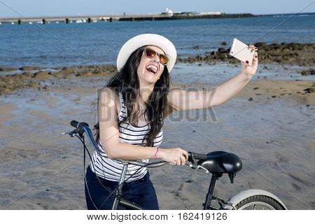 Young laughing woman in sunglasses with bike taking selfie on vacation in Lanzarote Gran Canaria Spain.