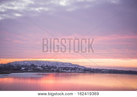 view on a lake with sunrice in cold winter morning
