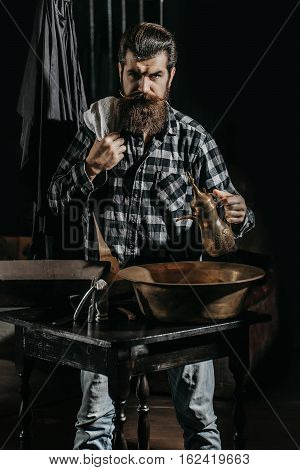 Handsome man bearded hipster brunette with long beard and moustache holds copper jug and towel on dark background
