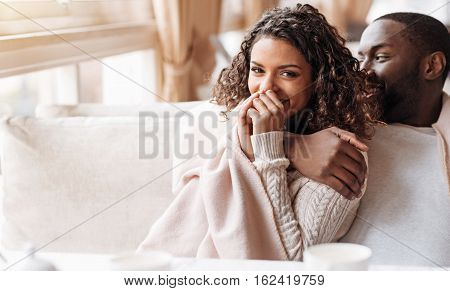 Funny time together. Positive funny delighted African American couple sitting in the cafe and being covered with a blanket while expressing love and laughing