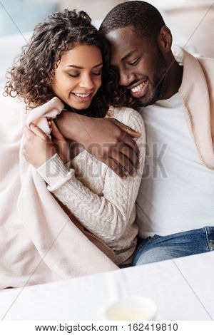 Happy to be in love. Positive young delighted African American couple sitting in the cafe and being covered with a blanket while expressing love and hugging