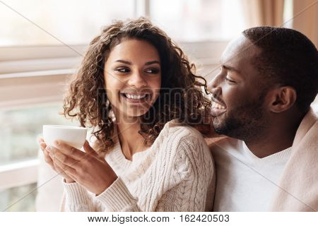 Enjoying our free time. Smiling merry positive African American couple sitting in the cafe and being covered with a blanket while expressing joy and drinking tea