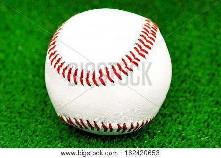 Close-up baseball ball on artificial green grass