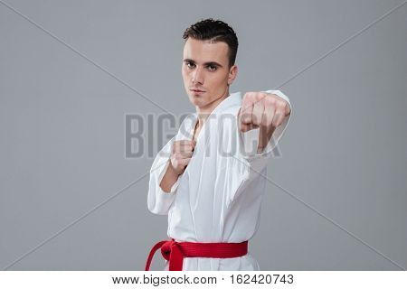 Picture of young sportsman dressed in kimono practice in karate isolated over grey background. Looking at camera.
