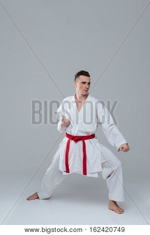 Photo of handsome young sportsman dressed in kimono practice in karate isolated over grey background. Looking aside.