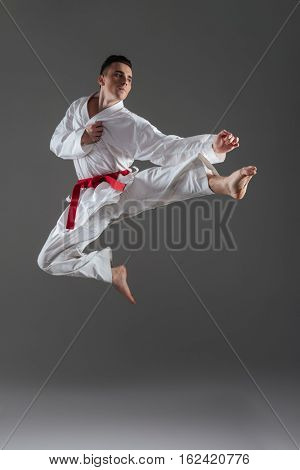 Attractive young sportsman dressed in kimono practice in karate isolated over grey background. Looking aside.