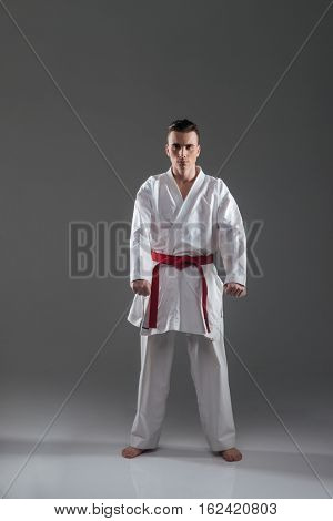 Picture of handsome sportsman in kimono posing isolated over grey background. Look at camera.
