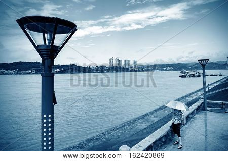 Woman holding a parasol overlooking the river Yichang Hubei China.