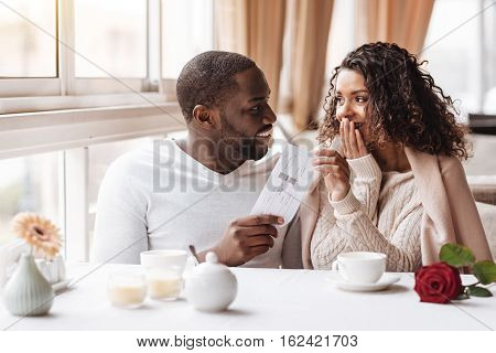 Romantic surprise from my boyfriend. Amazed positive overwhelmed African American woman sitting in the cafe with her boyfriend and receiving the ticket from him while expressing amazement