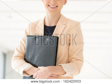 Portrait of smiling young businesswoman holding file in new office