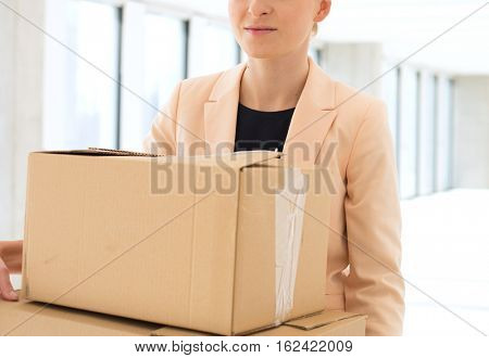 Young businesswoman carrying cardboard boxes in new office