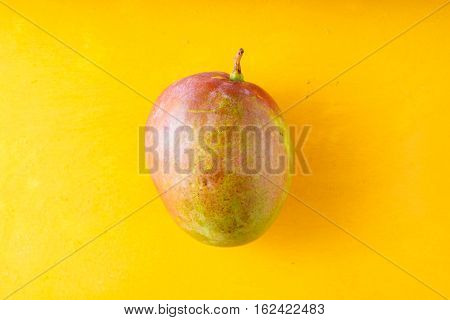 Mango on a yellow table horizontal colorful, whole