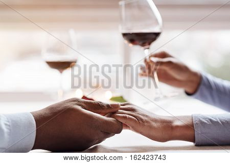 Closeness of soulmates. Delighted peaceful positive African American couple sitting in the restaurant and holding hands while expressing affection and holding wineglasses full of red wine